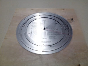 Circular slide-ruler in acrylic on plywood board.