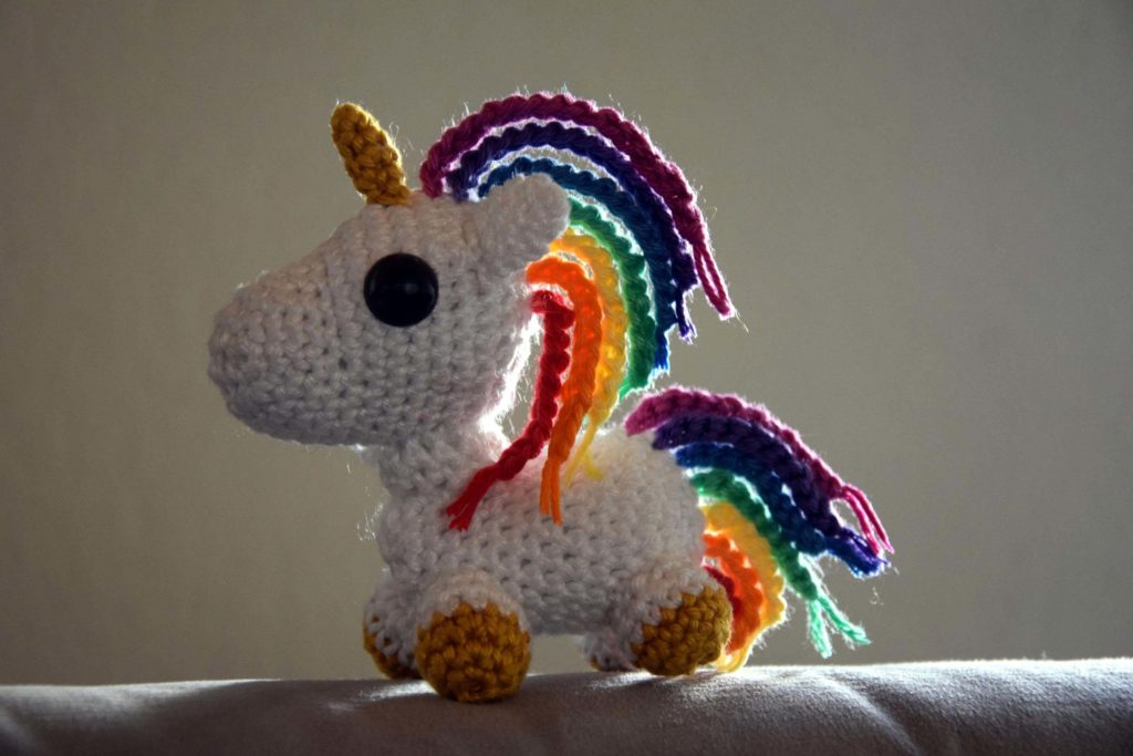 a small toy unicorn crocheted with yarn