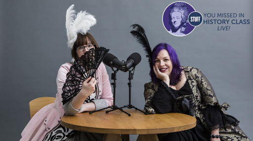 two women in 19th Century costumes with podcast microphones